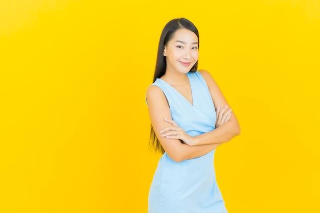 Portrait belle jeune femme asiatique sourire avec action sur le mur de couleur jaune