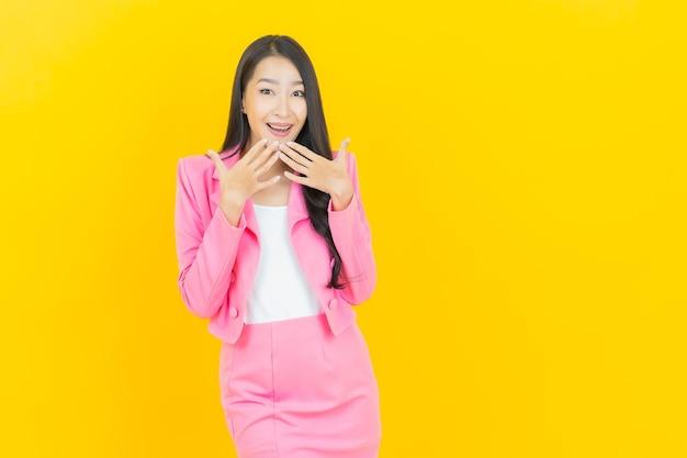 Portrait belle jeune femme asiatique sourire avec action sur mur de couleur jaune