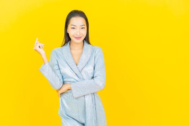 Portrait belle jeune femme asiatique sourire avec action sur mur jaune