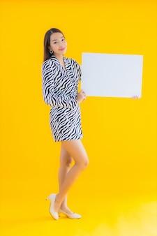 Portrait belle jeune femme asiatique sourire avec afficher le panneau d'affichage blanc vide sur jaune