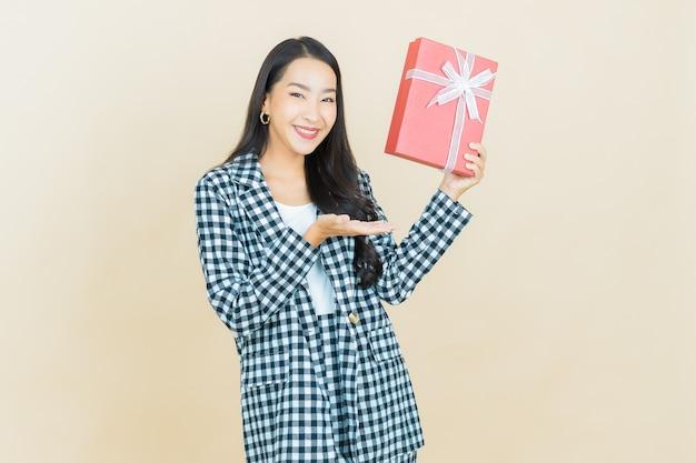 Portrait belle jeune femme asiatique sourire avec boîte-cadeau rouge sur beige