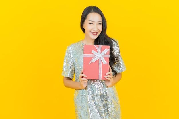 Portrait belle jeune femme asiatique sourire avec boîte-cadeau rouge sur jaune
