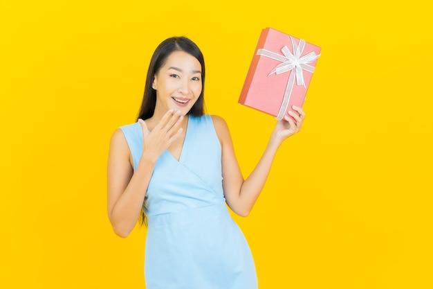 Portrait belle jeune femme asiatique sourire avec boîte-cadeau rouge sur le mur de couleur jaune