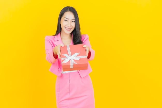 Portrait belle jeune femme asiatique sourire avec boîte-cadeau rouge sur mur de couleur jaune