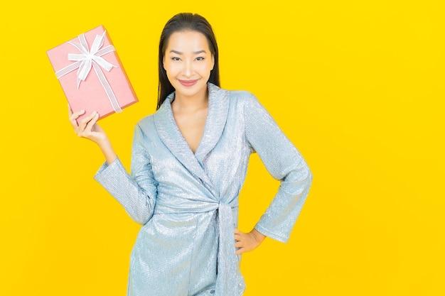 Portrait belle jeune femme asiatique sourire avec boîte-cadeau rouge sur mur jaune