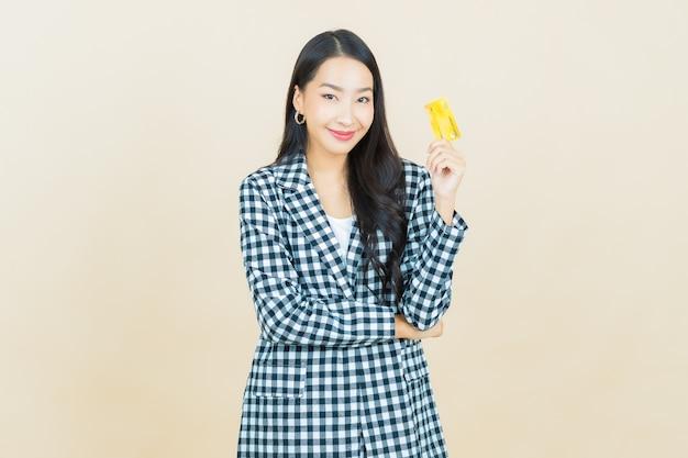 Portrait belle jeune femme asiatique sourire avec carte de crédit sur beige