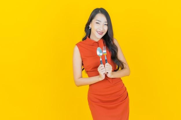 Portrait belle jeune femme asiatique sourire avec cuillère et fourchette sur jaune