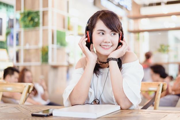 Portrait de la belle jeune femme asiatique sourire et écoute de la musique avec casque