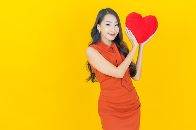 Portrait belle jeune femme asiatique sourire avec forme d'oreiller coeur sur jaune