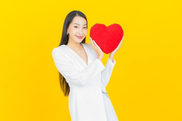 Portrait belle jeune femme asiatique sourire avec forme d'oreiller coeur