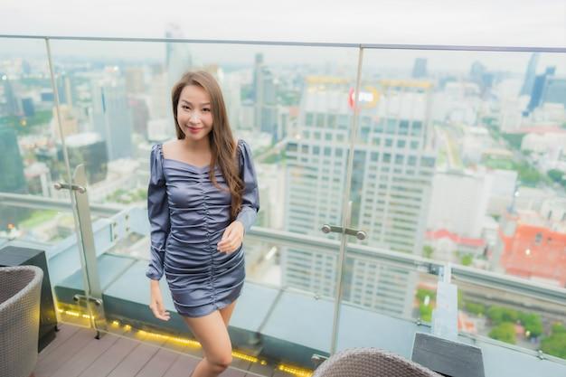 Portrait belle jeune femme asiatique sourire heureux sur le restaurant sur le toit autour de vue sur la ville