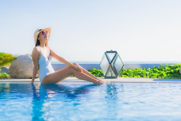 Portrait belle jeune femme asiatique sourire heureux se détendre autour de la piscine extérieure de l'hôtel resort