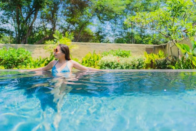 Portrait belle jeune femme asiatique sourire heureux se détendre et se détendre dans la piscine