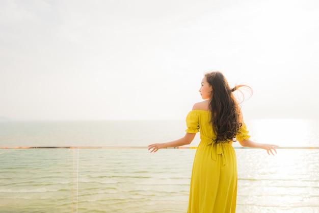 Portrait belle jeune femme asiatique sourire heureux et vous détendre sur le balcon extérieur avec mer, plage et oce