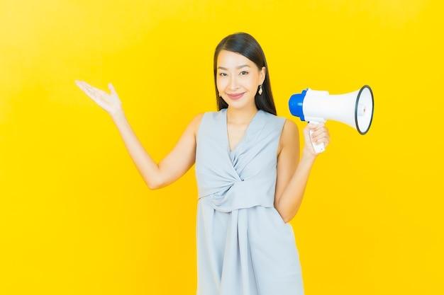 Portrait belle jeune femme asiatique sourire avec mégaphone