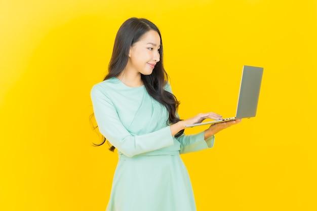 Portrait belle jeune femme asiatique sourire avec ordinateur portable sur jaune