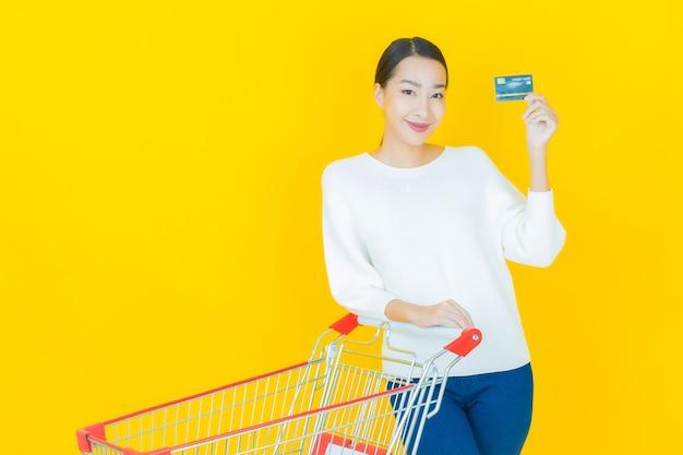 Portrait belle jeune femme asiatique sourire avec panier d'épicerie du supermarché sur jaune