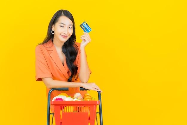 Portrait belle jeune femme asiatique sourire avec panier d'épicerie de supermarché sur jaune
