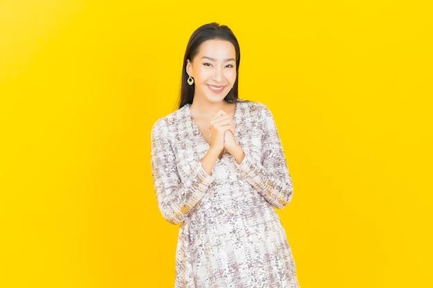 Portrait belle jeune femme asiatique sourire posant sur jaune