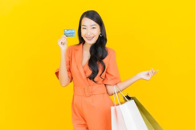 Portrait belle jeune femme asiatique sourire avec sac à provisions sur jaune