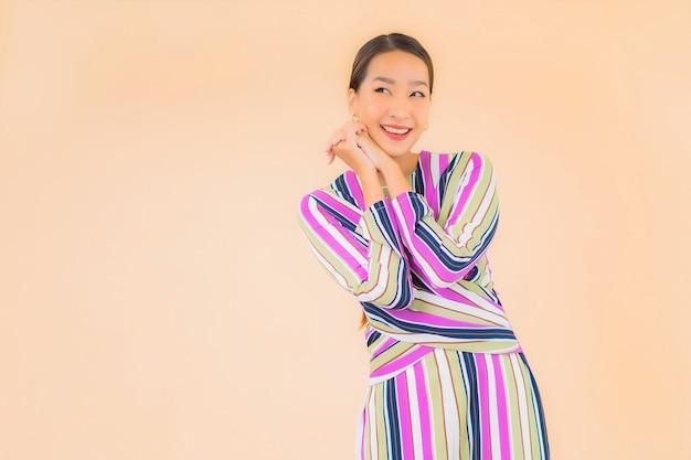 Portrait belle jeune femme asiatique sourire se détendre en action sur la couleur
