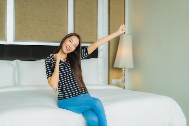 Portrait belle jeune femme asiatique sourire se détendre sur le lit à l'intérieur de la chambre