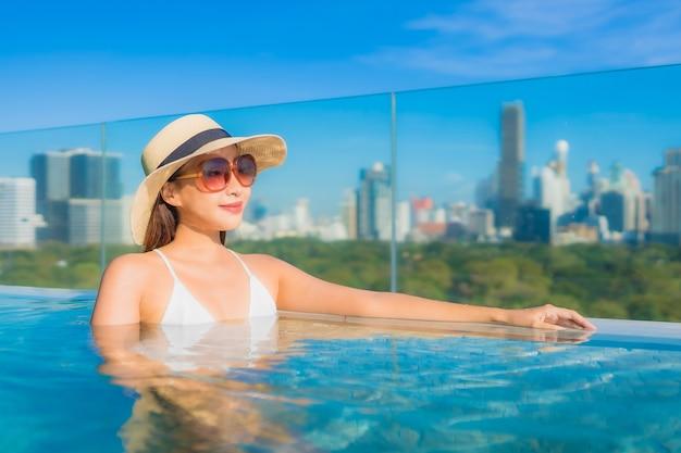 Portrait belle jeune femme asiatique sourire se détendre loisirs autour de la piscine extérieure avec vue sur la ville