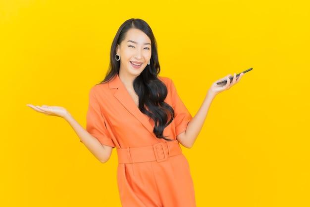 Portrait belle jeune femme asiatique sourire avec téléphone mobile intelligent sur jaune