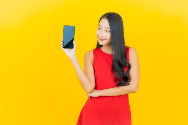 Portrait belle jeune femme asiatique sourire avec téléphone mobile intelligent sur mur jaune