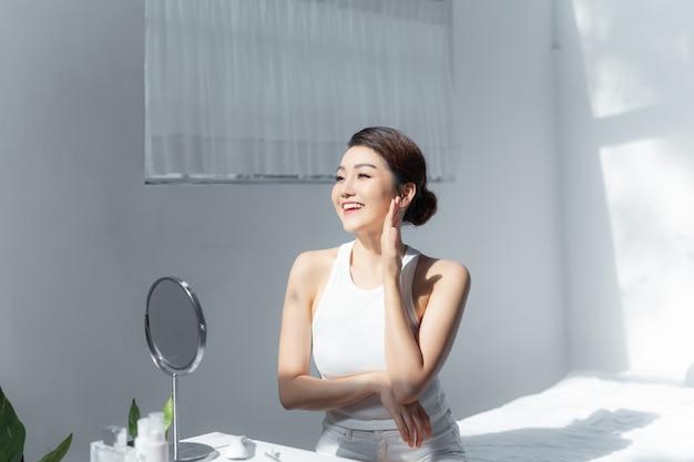 Portrait de la belle jeune femme asiatique sourire tout en se réveillant en bonne santé et bien-être avec le lever du soleil au matin dans la chambre