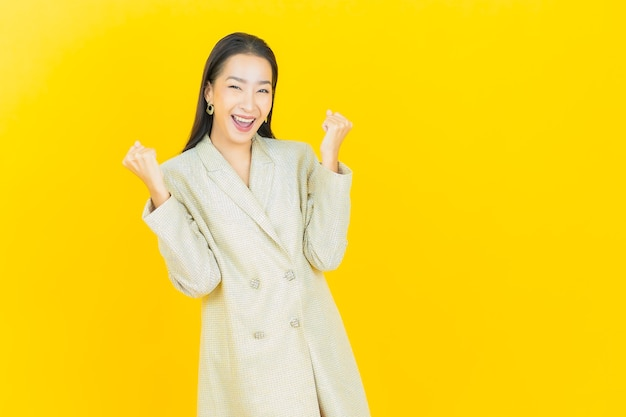 Portrait belle jeune femme asiatique sourit avec action sur mur de couleur
