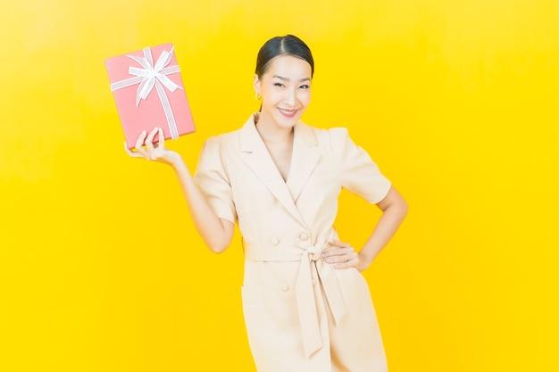 Portrait belle jeune femme asiatique sourit avec une boîte cadeau rouge sur un mur de couleur