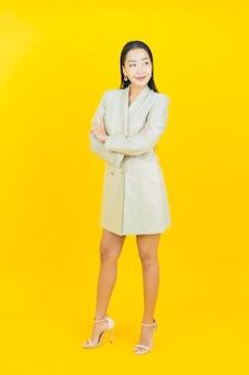 Portrait belle jeune femme asiatique sourit avec les bras croisés sur le mur de couleur