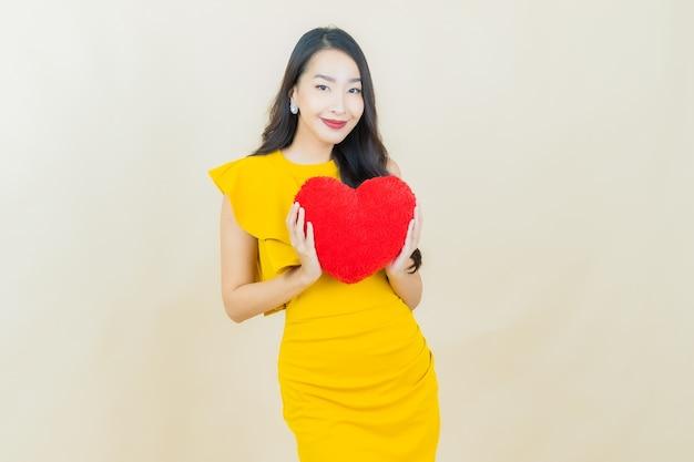 Portrait belle jeune femme asiatique sourit avec forme d'oreiller coeur sur mur beige
