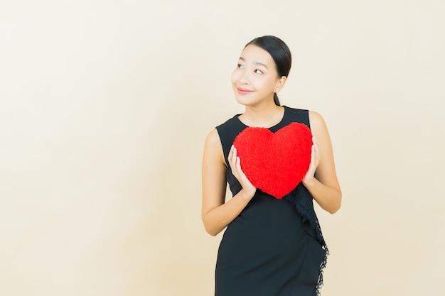 Portrait belle jeune femme asiatique sourit avec forme d'oreiller coeur sur mur de couleur