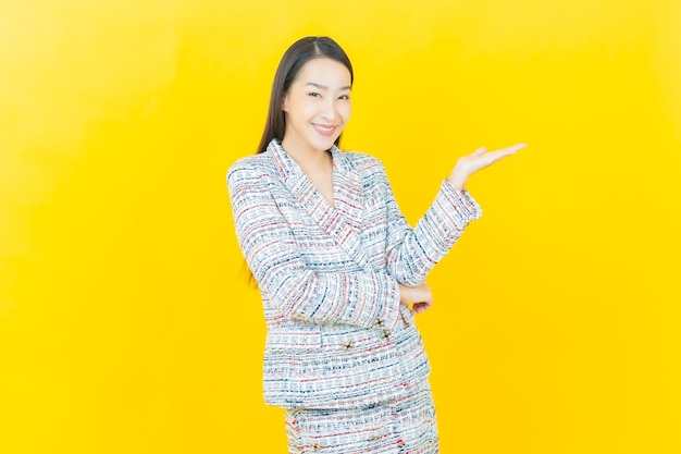 Portrait belle jeune femme asiatique sourit sur le mur de couleur