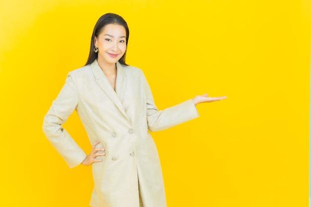 Portrait belle jeune femme asiatique sourit sur mur jaune