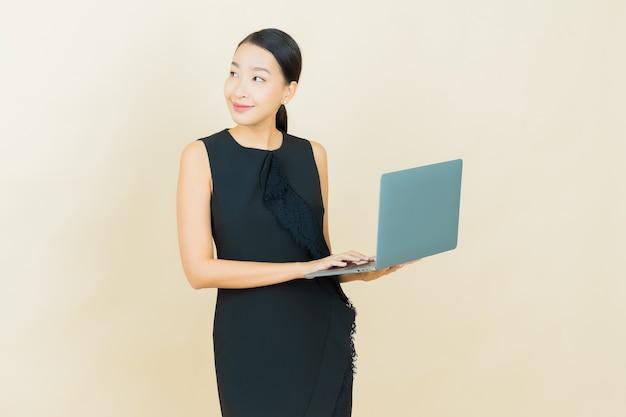 Portrait belle jeune femme asiatique sourit avec ordinateur portable sur mur isolé