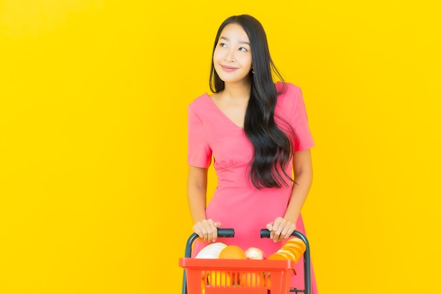 Portrait belle jeune femme asiatique sourit avec panier d'épicerie de supermarché sur mur jaune