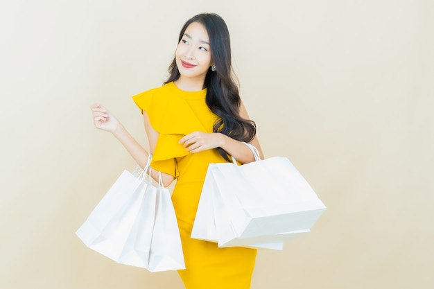 Portrait belle jeune femme asiatique sourit avec sac à provisions sur mur beige