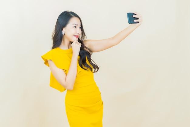 Portrait belle jeune femme asiatique sourit avec un téléphone portable intelligent sur un mur beige