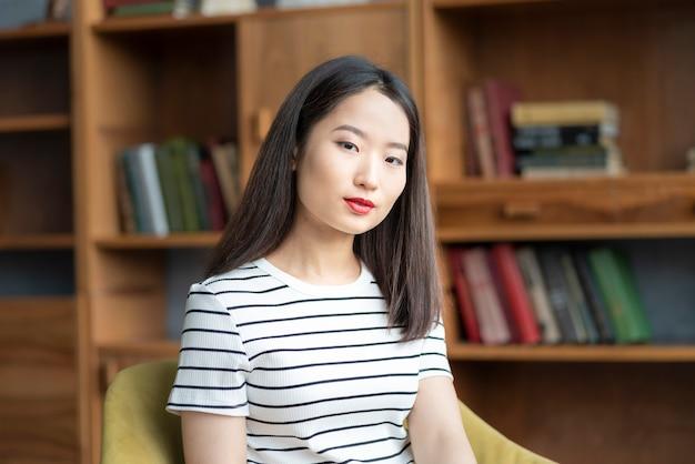 Portrait de la belle jeune femme asiatique en t-shirt rayé assis dans une chaise