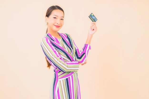 Portrait belle jeune femme asiatique avec téléphone mobile intelligent et carte de crédit sur la couleur