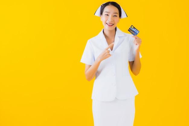 Portrait belle jeune femme asiatique thai infirmière avec carte de crédit