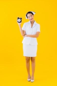 Portrait belle jeune femme asiatique thai infirmière avec horloge ou alarme