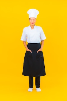 Portrait belle jeune femme asiatique en uniforme de chef ou de cuisinier avec chapeau sur fond isolé jaune