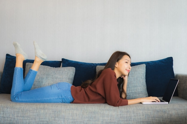 Portrait belle jeune femme asiatique utilise un ordinateur portable sur un canapé à l'intérieur du salon
