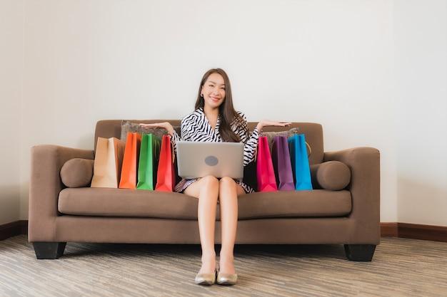 Portrait belle jeune femme asiatique utilise un ordinateur portable, un téléphone mobile intelligent ou de l'argent comptant pour faire des achats en ligne sur un canapé à l'intérieur du salon
