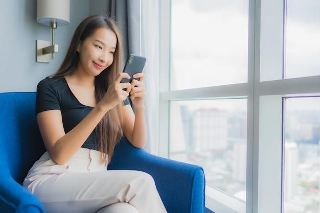 Portrait belle jeune femme asiatique utilise un téléphone mobile intelligent sur un canapé dans le salon