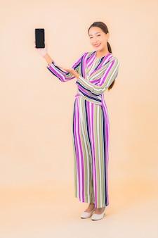 Portrait belle jeune femme asiatique utilise un téléphone mobile intelligent sur la couleur